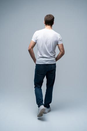 Vista posterior de un joven casual caminando y mirando al lado sobre fondo gris.