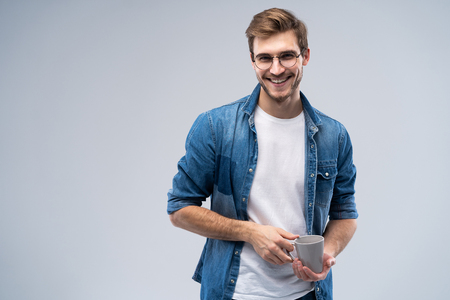 Handsome smiling man with cup of coffee isolated on gray background. 写真素材 - 116347669