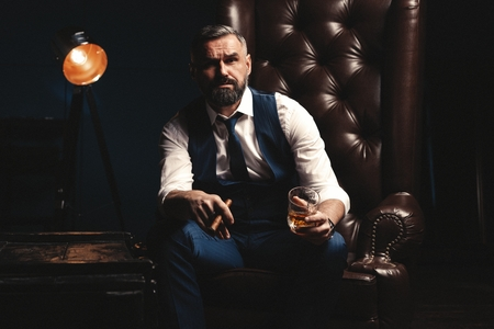 Attractive man with cigar and a glass whiskey Фото со стока