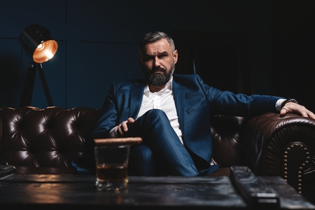 Attractive man with cigar and a glass whiskey Imagens