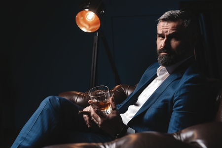Attractive man with cigar and a glass whiskey Reklamní fotografie
