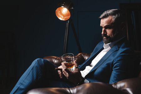 Attractive man with cigar and a glass whiskey Stock Photo