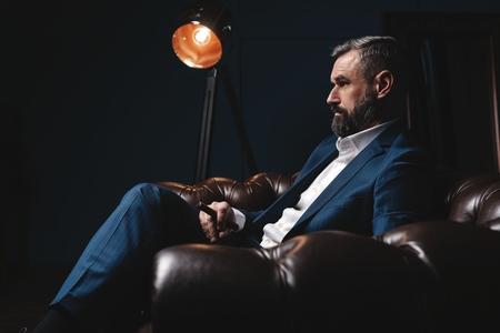 Hombre atractivo con cigarro y un vaso de whisky