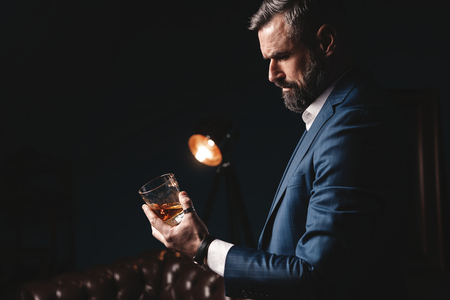 Degustation, tasting. Man with beard holds glass of brandy. Tasting and degustation concept. Bearded businessman in elegant suit with glass of whiskey Фото со стока