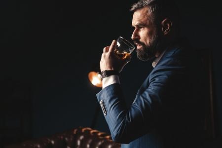 Degustazione, degustazione. L'uomo con la barba tiene un bicchiere di brandy. Degustazione e concetto di degustazione. Uomo d'affari barbuto in abito elegante con bicchiere di whisky Archivio Fotografico