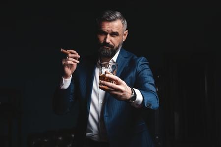 Aantrekkelijke man met sigaar en een glas whisky