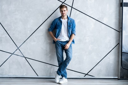 Modern and casual. Full length of handsome young man in jeans shirt looking at camera with smile while standing. Stock Photo
