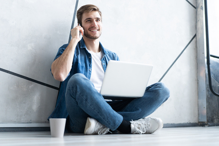 Young caucasian man sitting over gray wall using computer laptop and smartphone.