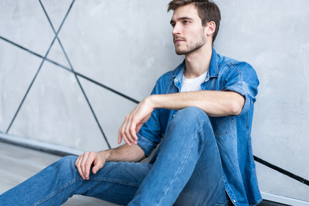Handsome happy man sitting at the floor over gray background. Stock Photo