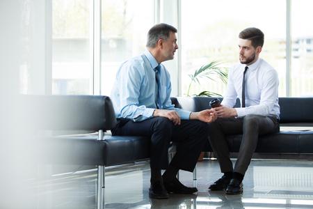 Älterer Geschäftsmann, der ein digitales Tablet verwendet, um Informationen mit einem jüngeren Kollegen in einer modernen Geschäftslounge zu besprechen.