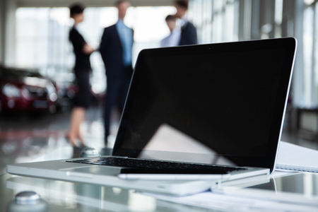 Closeup photo of laptop computer with open top and business people in background.