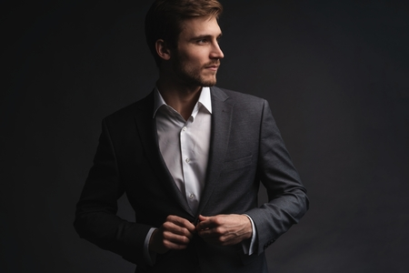 Portrait of serious handsome man in gray suit buttoning jacket