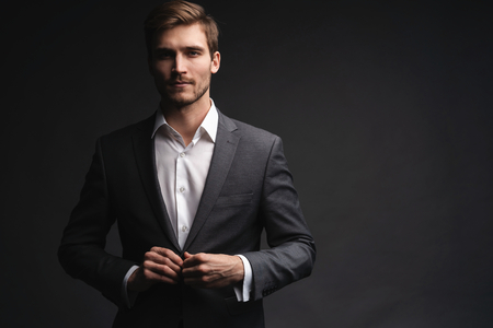 Portrait of serious handsome man in gray suit buttoning jacket Stock Photo