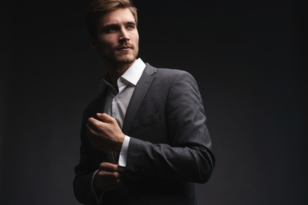 Perfect to the last detail. Handsome young businessman adjusting his sleeves while standing against gray background. Reklamní fotografie