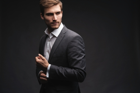 Perfect to the last detail. Handsome young businessman adjusting his sleeves while standing against gray background. Foto de archivo