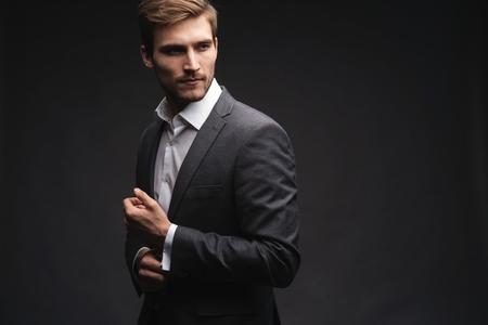 Perfecta hasta el último detalle. Apuesto joven empresario ajustando sus mangas mientras está de pie contra el fondo gris.