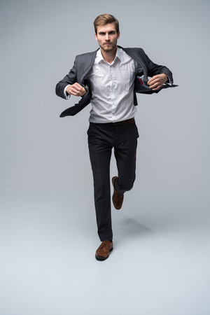 Confidence in every move. Full length of handsome young man in full suit adjsuting his jacket while walking ahead on gray background