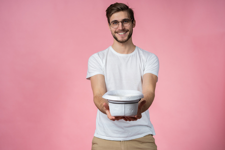 Happy attractive young man holding hat and asking for money over pink background.