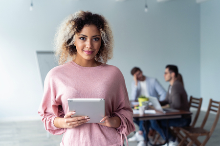 Business woman standing in foreground with a tablet in her hands, her co-workers discussing business matters in the background. Stock Photo