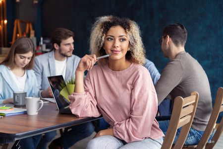 Happy to be in team. Beautiful cheerful African woman looking at camera with smile while sitting at the office table with her coworkers. Imagens - 117979105