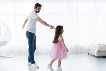 I love you, dad! Handsome young man is dancing at home with his little girl. Happy Fathers Day! Stock Photo