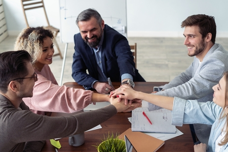 Business partners hands on top of each other symbolizing companionship. Stock Photo