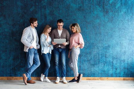 Het verbonden team is een efficiënt team. Groep zakenmensen die samen draadloze technologie gebruiken terwijl ze in de rij staan tegen een blauwe achtergrond.