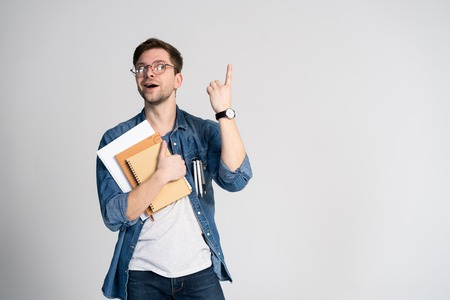I have got brilliant idea. Caucasian cheerful man, raises index finger, has intriguing plan isolated over white background with copy space Stockfoto