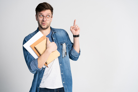 I have got brilliant idea. Caucasian cheerful man, raises index finger, has intriguing plan isolated over white background with copy space Banco de Imagens