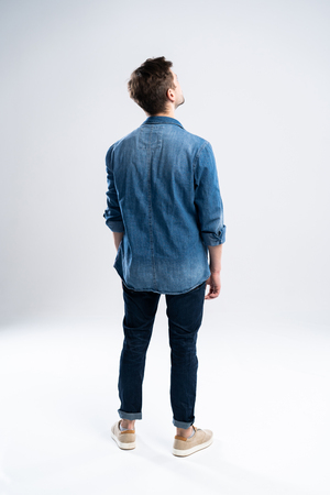 back view of a casual man standing on white background.