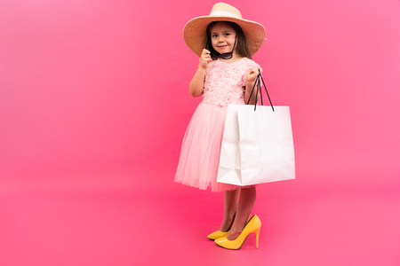Happy lovely moments of shopping time with cute little girl in dress standing in mother`s big shoes with white packages in hands isolated on pink background