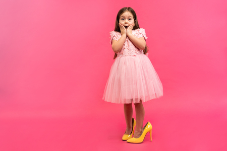 Amazing excited happy girl in dress in mama`s shoes expressing to camera isolated on pink background. Brightful emotions.