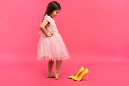 funny child girl fashionista in dress going to put on big mothers yellow shoes on colored background. Standard-Bild