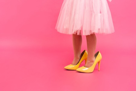 Little girl in oversized shoes with space for text, closeup on legs isolated on pink.