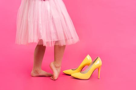 Klein meisje in oversized schoenen met ruimte voor tekst, close-up op benen geïsoleerd op roze.