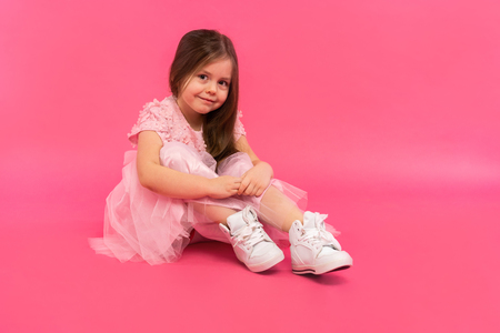 Little girl, studio portrait of beautiful child in pink dress over pink background. Stockfoto