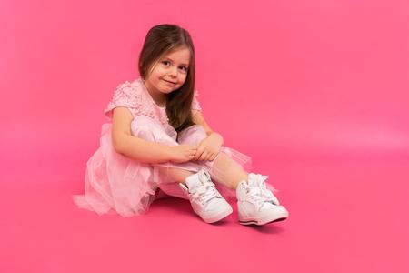 Little girl, studio portrait of beautiful child in pink dress over pink background. 免版税图像