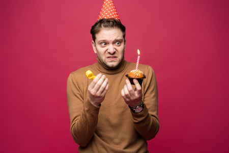 Picture of unhappy stressed young man having unhappy look, feeling tired and worn out with birthday party preparations, standing in studio Foto de archivo - 117975900