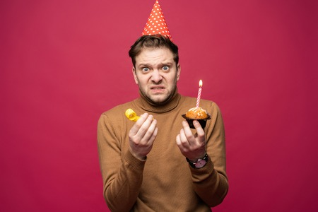 Picture of unhappy stressed young man having unhappy look, feeling tired and worn out with birthday party preparations, standing in studio Foto de archivo - 117975902