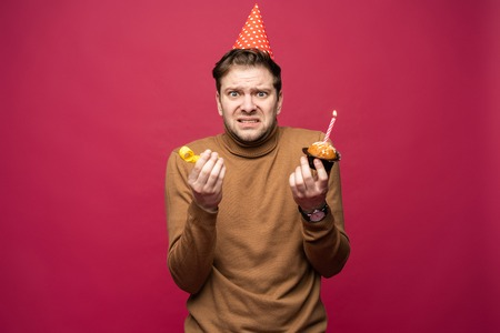Picture of unhappy stressed young man having unhappy look, feeling tired and worn out with birthday party preparations, standing in studio Foto de archivo - 117975901