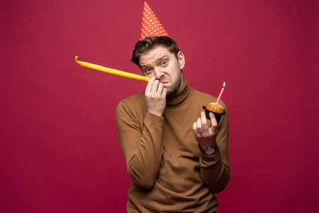 Picture of unhappy stressed young man having unhappy look, feeling tired and worn out with birthday party preparations, standing in studio Фото со стока