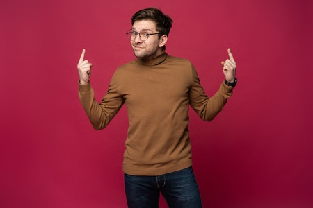 Portrait of a happy young man pointing fingers up at copy space isolated over pink background.