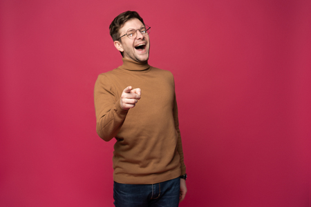 Indoor shot of cheerful man in spectacles and casual clothes indicates happily at you, chooses to compete, has positive expression. Handsome clever student makes choice, isolated on pink wall. Banco de Imagens