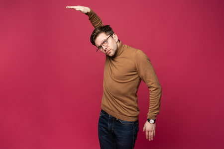 Portrait of a joyful young man pointing hands away at copy space on his palm isolated over pink background. Stok Fotoğraf