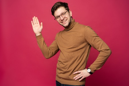 Portrait of smiling man with hand raised in greeting. High five conceptю