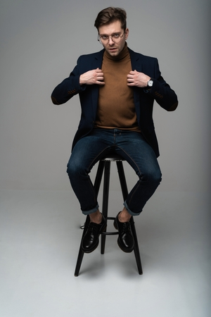 full length portrait of a young fashion man sitting on a chair and looking into the camera on a gray background.