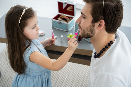 Cute little daughter and her handsome young dad in crowns are playing together in childs room. Girl is doing her dad a makeup.