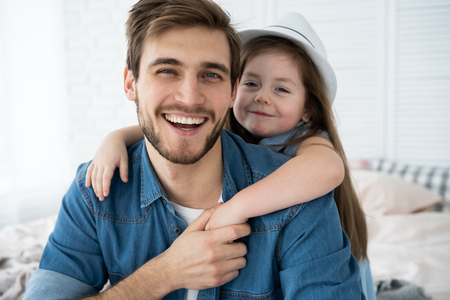 Portrait of handsome father and his cute daughter hugging, looking at camera and smiling while sitting on sofa at home. 版權商用圖片