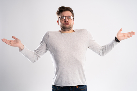 Angry disappointed man spreads hands with indignation, looks with uncertainty, wears optical glasses, isolated over white background. What I did wrong?