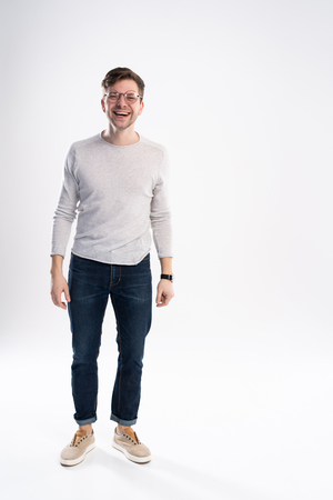full body picture of a smiling casual man standing on white background.